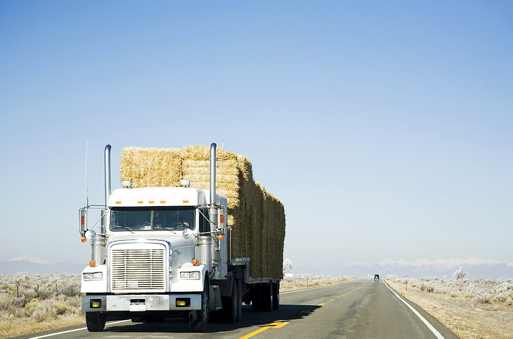 Truck hauling hay on rural road, Colorado, USA