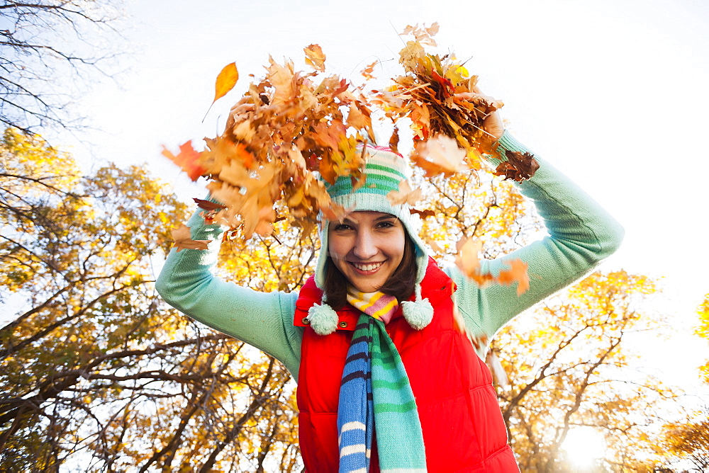Portrait of smiling young woman throwing dry leaves in autumn forest, Alpine, Utah