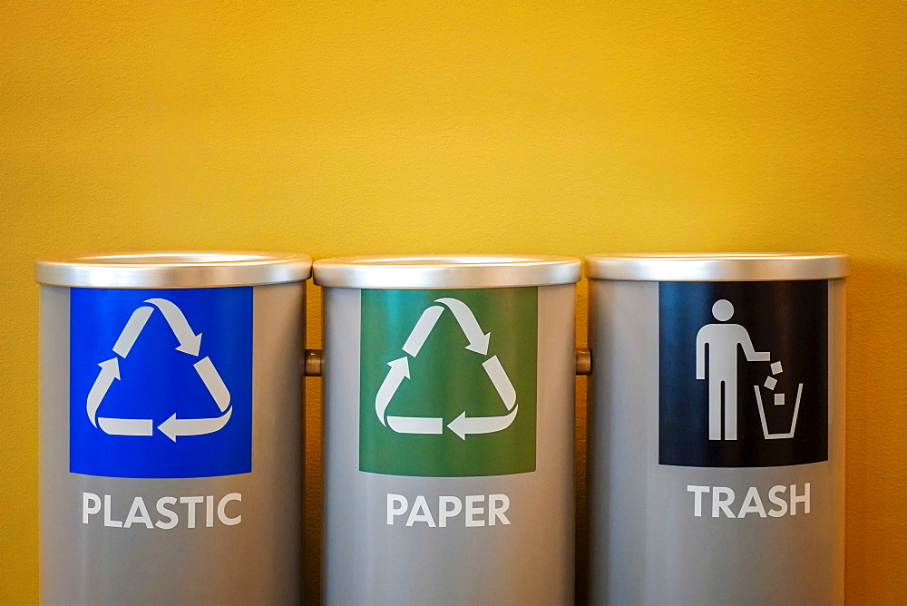 Recycling bins on yellow background