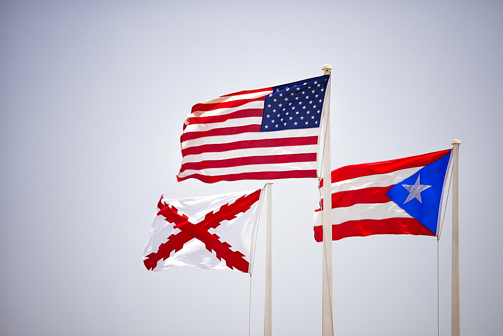 Morro Castle, American, Puerto Rican and naval flags flying against blue sky, El Morro, San Juan, Puerto Rico