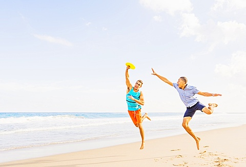 Young men playing plastic disc on beach, Jupiter, Florida