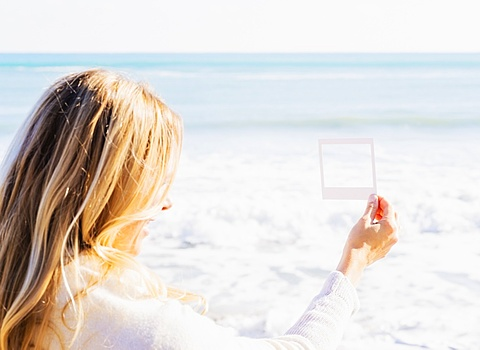 Woman holding small picture frame, Jupiter, Florida