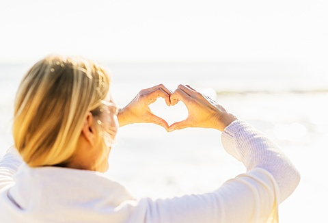 Woman showing heart shape with hands