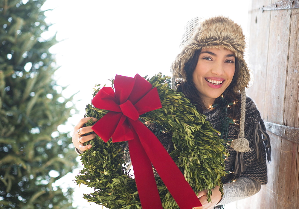 Portrait of young woman holding Christmas wreath