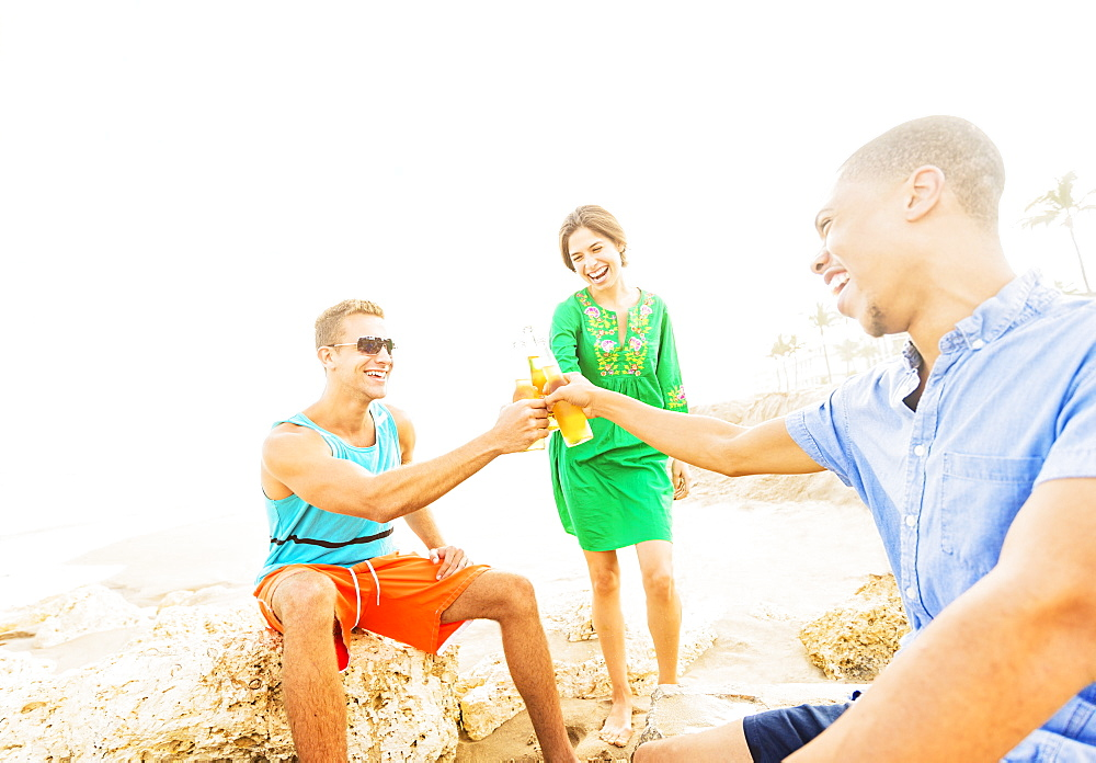 Young people drinking beer on beach, Jupiter, Florida