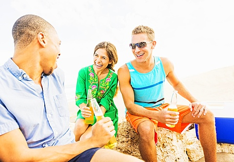 Young people drinking beer on beach