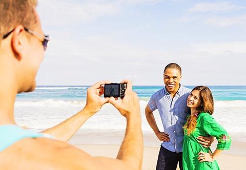 Young man taking photo of couple on beach, Jupiter, Florida