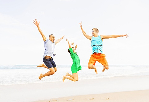 Young people jumping on beach, Jupiter, Florida