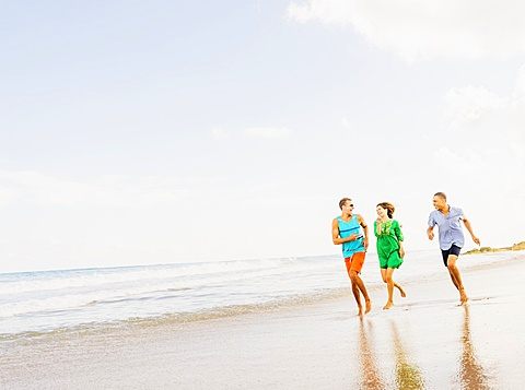 Young people running on beach, Jupiter, Florida