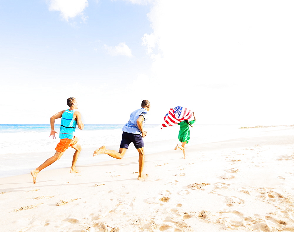 Young people running with American flag on beach, Jupiter, Florida