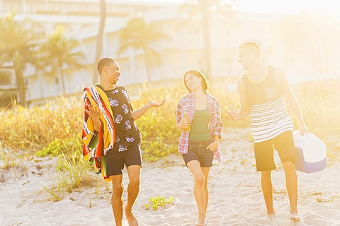 Young people walking on beach at sunset, Jupiter, Florida