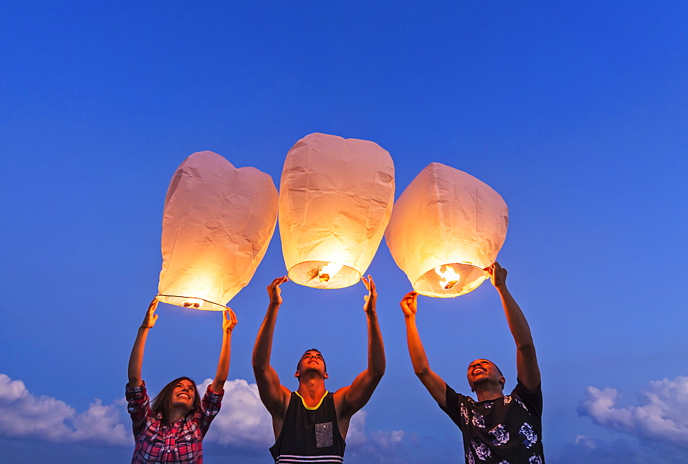 Young people with illuminated lanterns at sunset