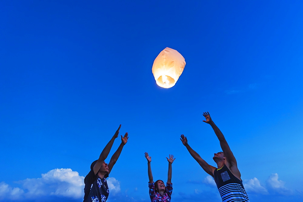 Young people with illuminated lantern at sunset