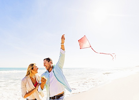 Couple on beach with kite, Jupiter, Florida
