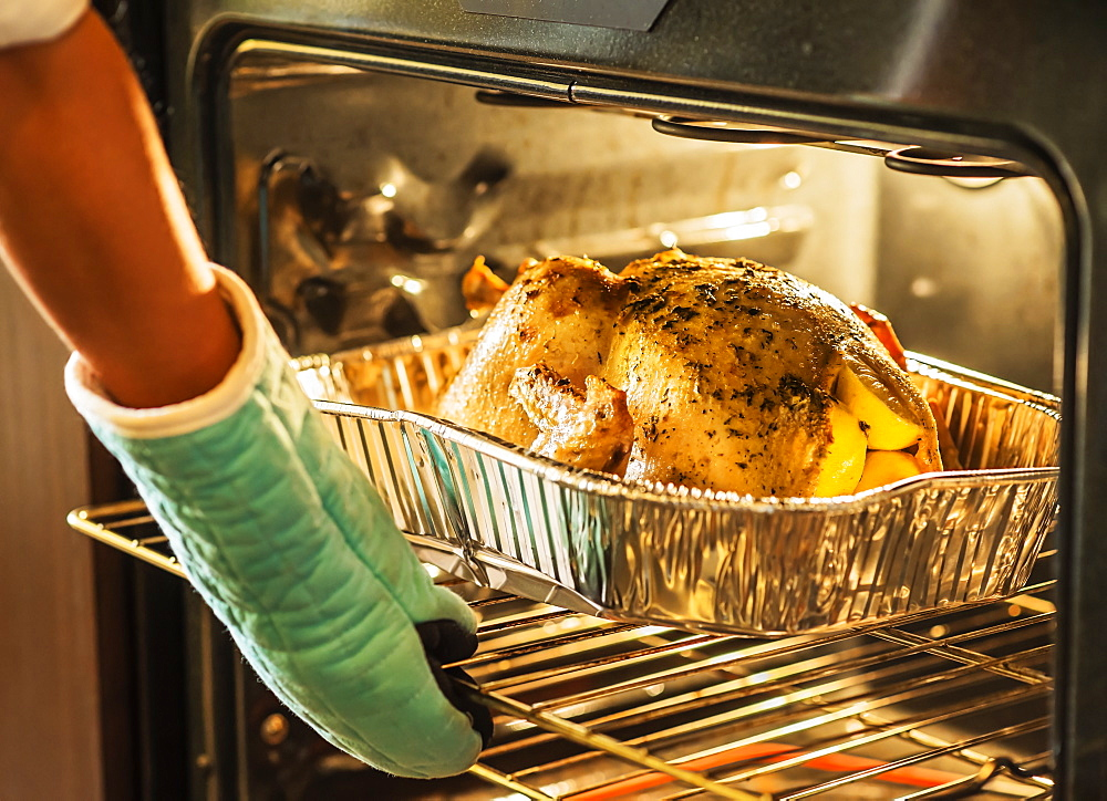 Woman checking turkey in oven