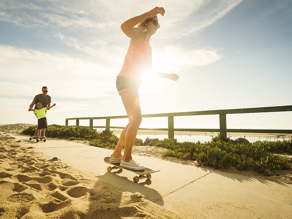 Parents skateboarding with their son (6-7), Laguna Beach, California