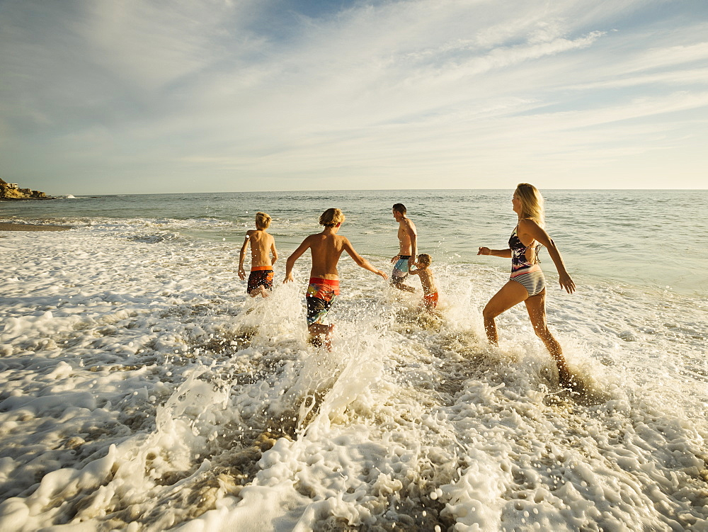Family with three children (6-7, 10-11, 14-15) running on beach, Laguna Beach, California - 1178-24037