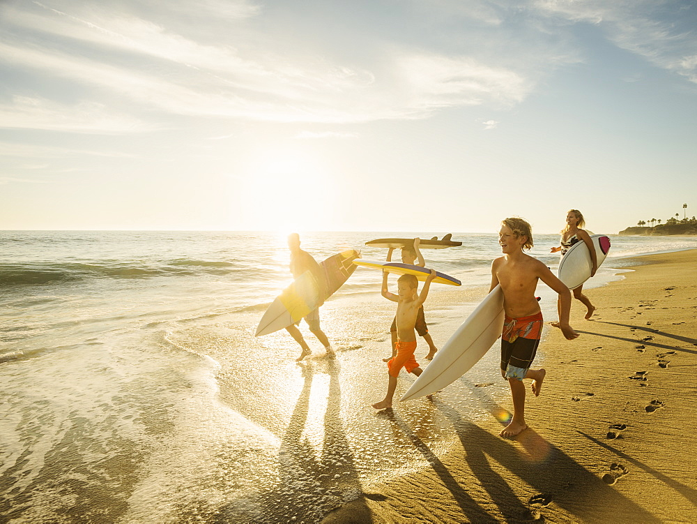 Family with three children (6-7, 10-11, 14-15) with surfboards on beach, Laguna Beach, California