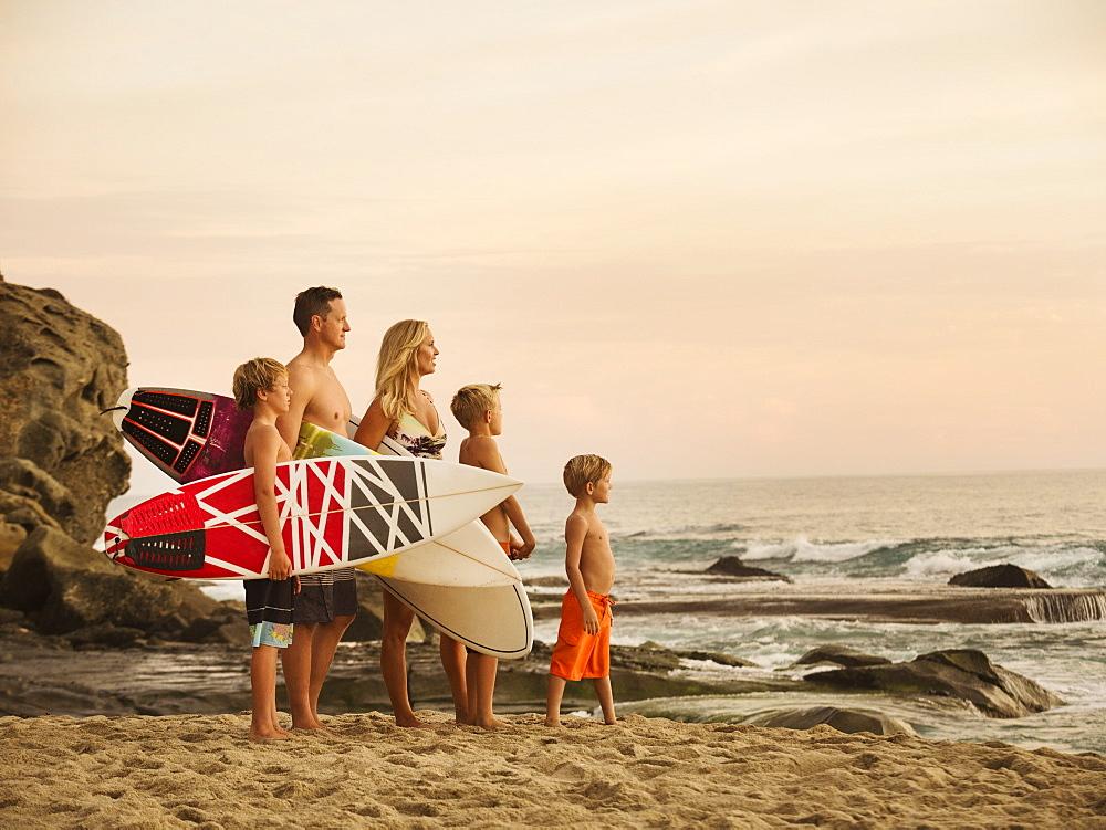 Family with three children (6-7, 10-11, 14-15) looking at sea, Laguna Beach, California