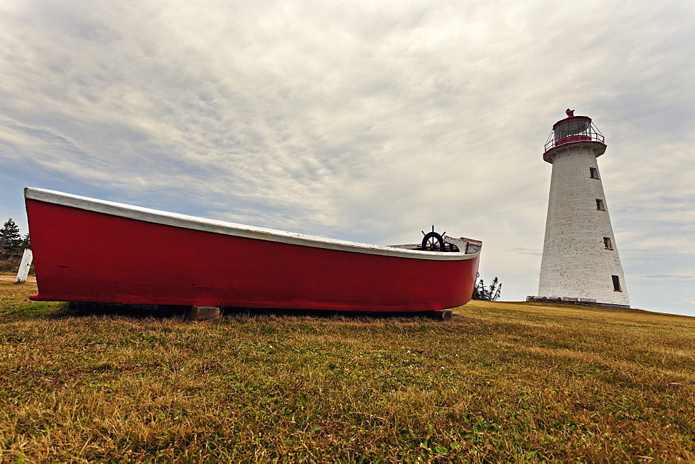 Low angle view of Point Prim Lighthouse and red boat, Prince Edward Island, New Brunswick, Canada