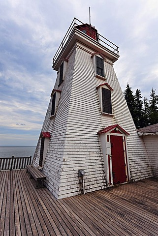 Low angle view of lighthouse and wooden pier, Prince Edward Island, New Brunswick, Canada