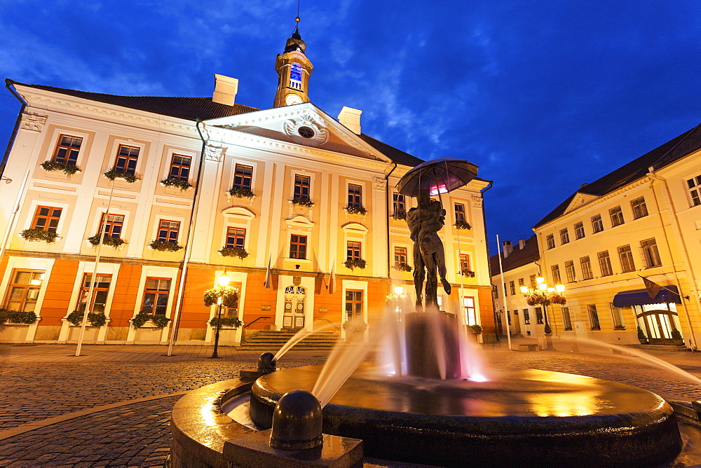 Kissing Students Fountain against illuminated building, Estonia