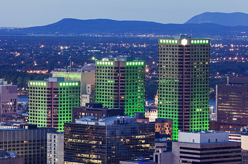Three skyscrapers illuminated with green light towering over cityscape, Quebec, Canada