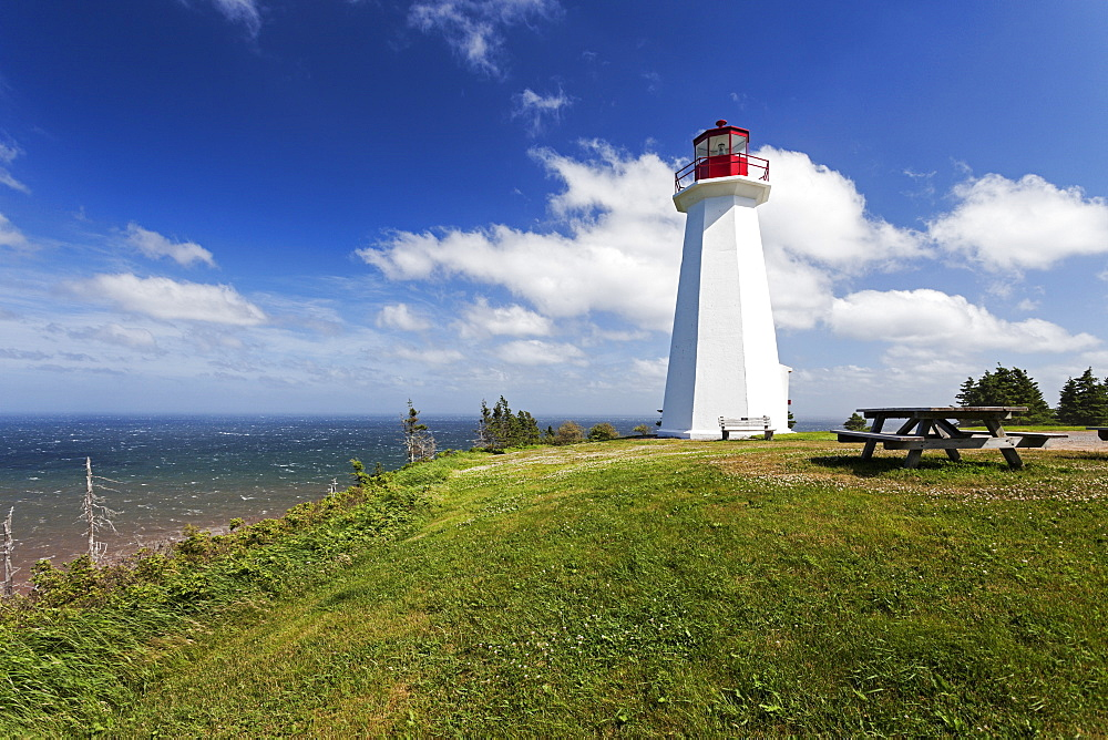 Cape George Lighthouse on green seaside cliff, Nova Scotia, Canada