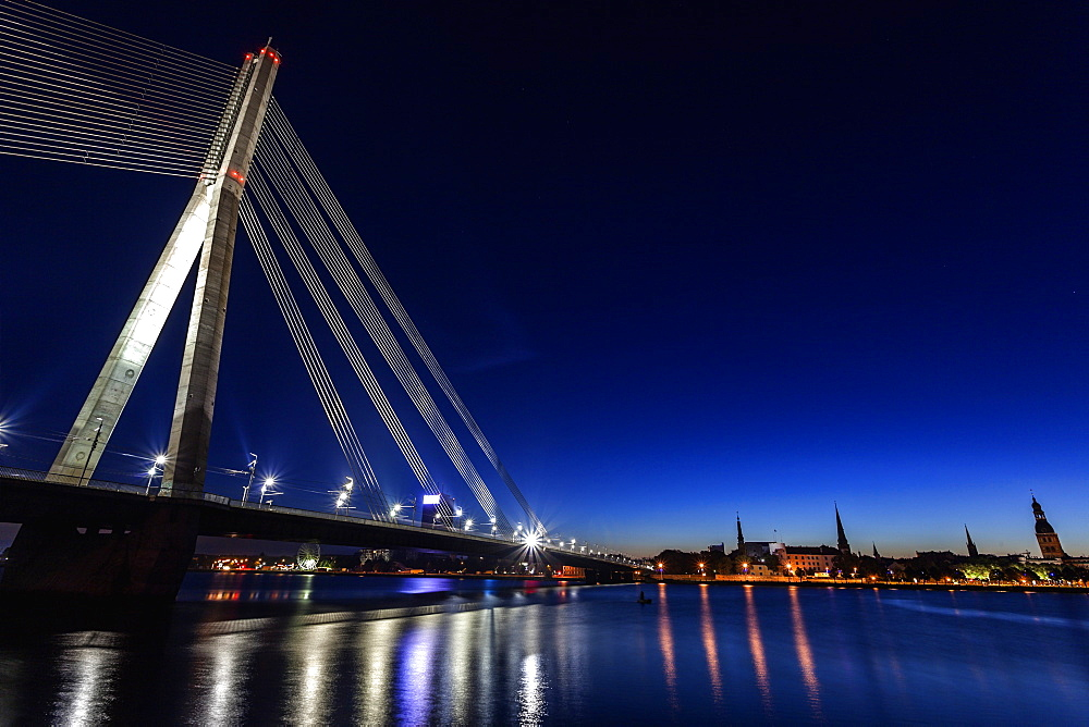 Illuminated Vansu Bridge reflecting in river, Latvia