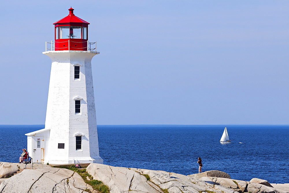 Peggy's Point Lighthouse against sea with lone sailboat, Nova Scotia, Canada