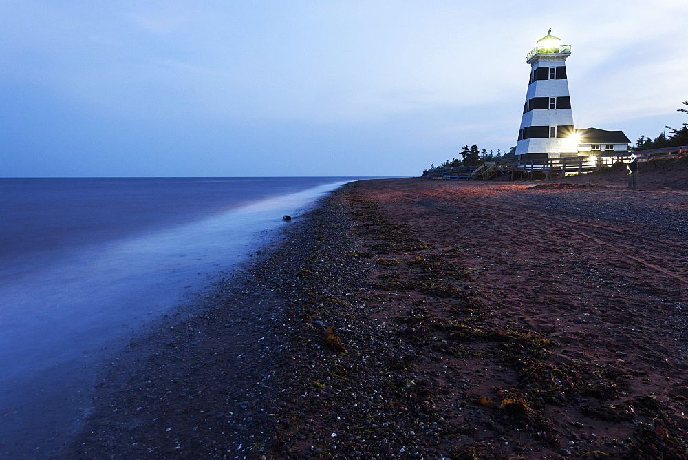 Illuminated West Point Lighthouse seen from empty beach, Prince Edward Island, New Brunswick, Canada