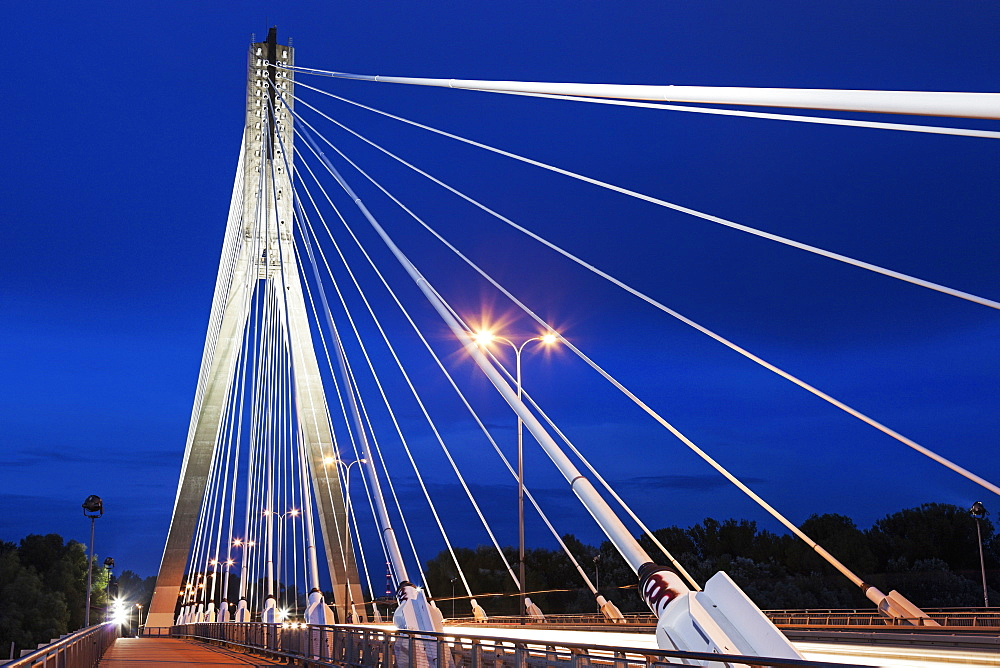 Tower and cables of illuminated Swietokrzyski Bridge against night sky, Poland