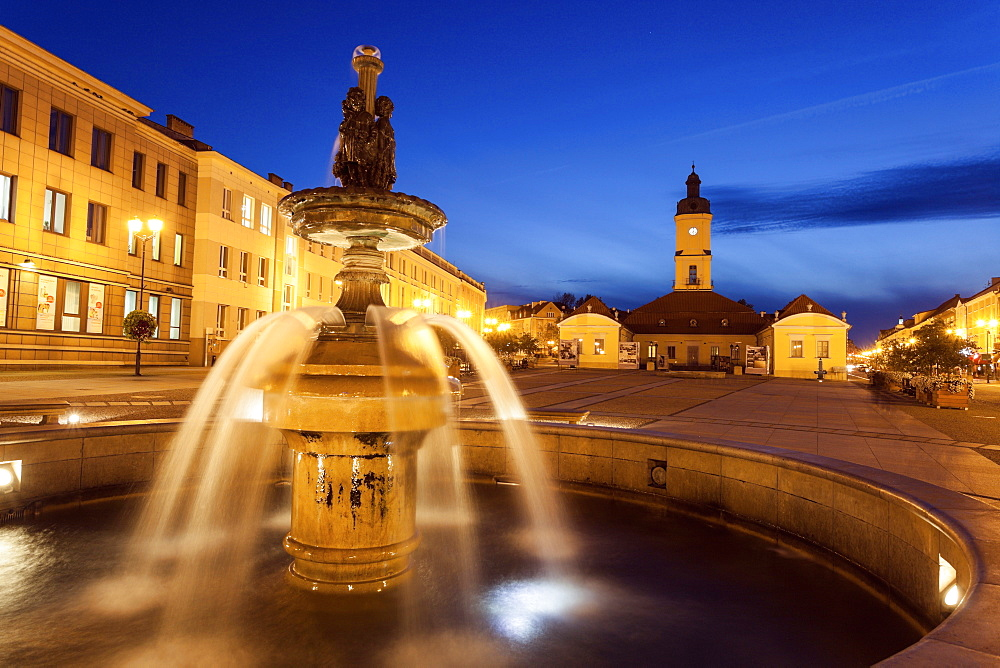 Poland, Podlaskie, Bialostok Fountain on illuminated town square, Poland
