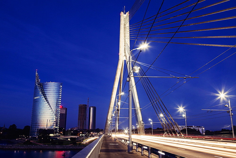 Suspension bridge with skyscrapers on background at night, Latvia