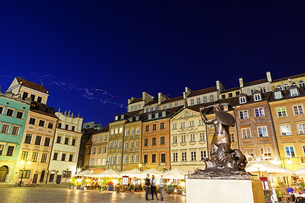 Sculpture of mermaid on town square at night, Poland