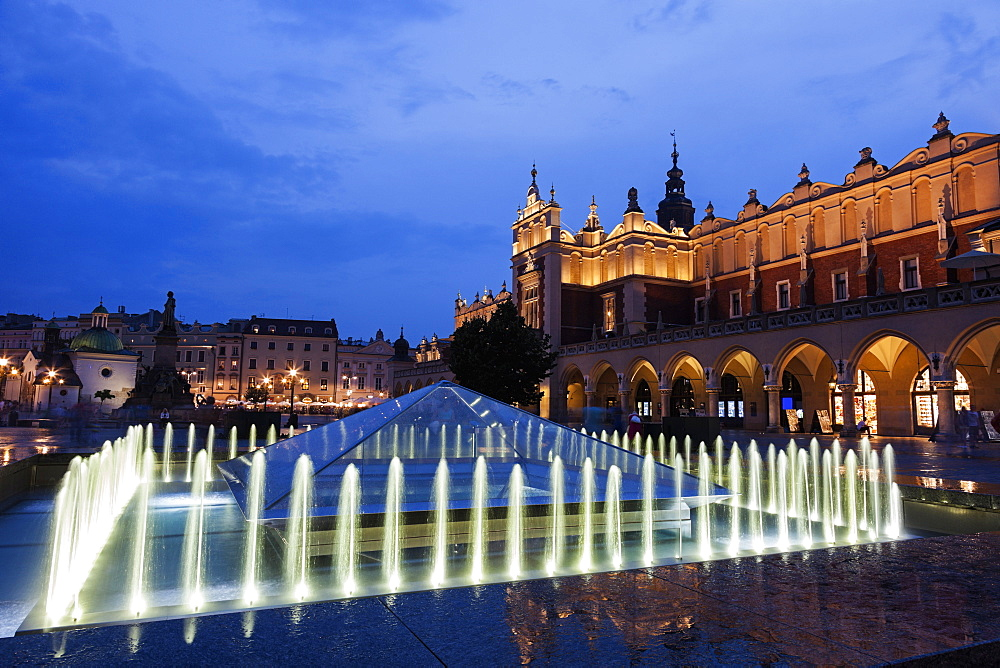 Illuminated fountain and Cloth Hall at dusk, Poland