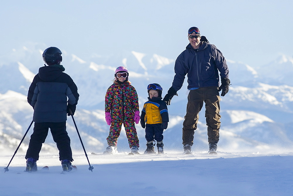 Father skiing with children (6-7, 8-9), Whitefish, Montana, USA