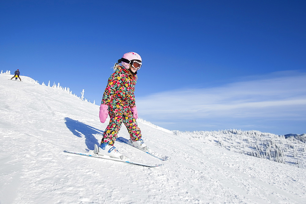 Girl (8-9) skiing in mountains, Whitefish, Montana USA