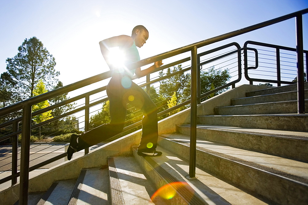 Woman running on steps, Berkeley, California, USA