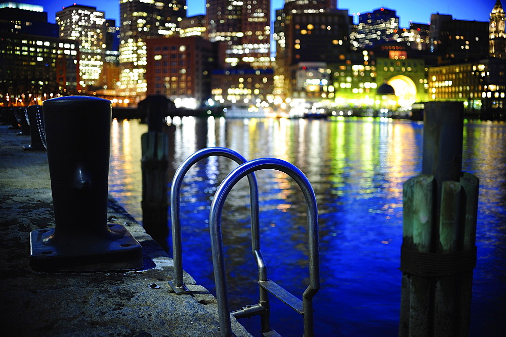 Metal ladder along commercial pier with Boston Waterfront in background, Boston, Massachusetts