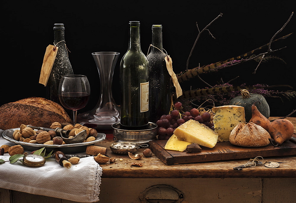 Still life with wine bottles, selection of cheese, bread and nuts on wooden table, studio shot