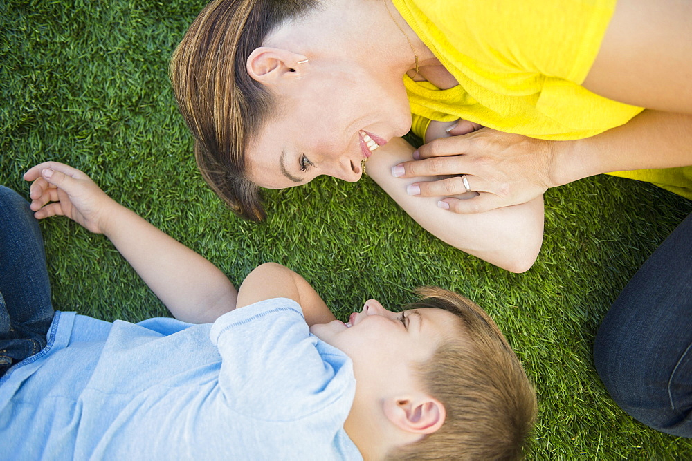 Mother and son (6-7) relaxing on grass