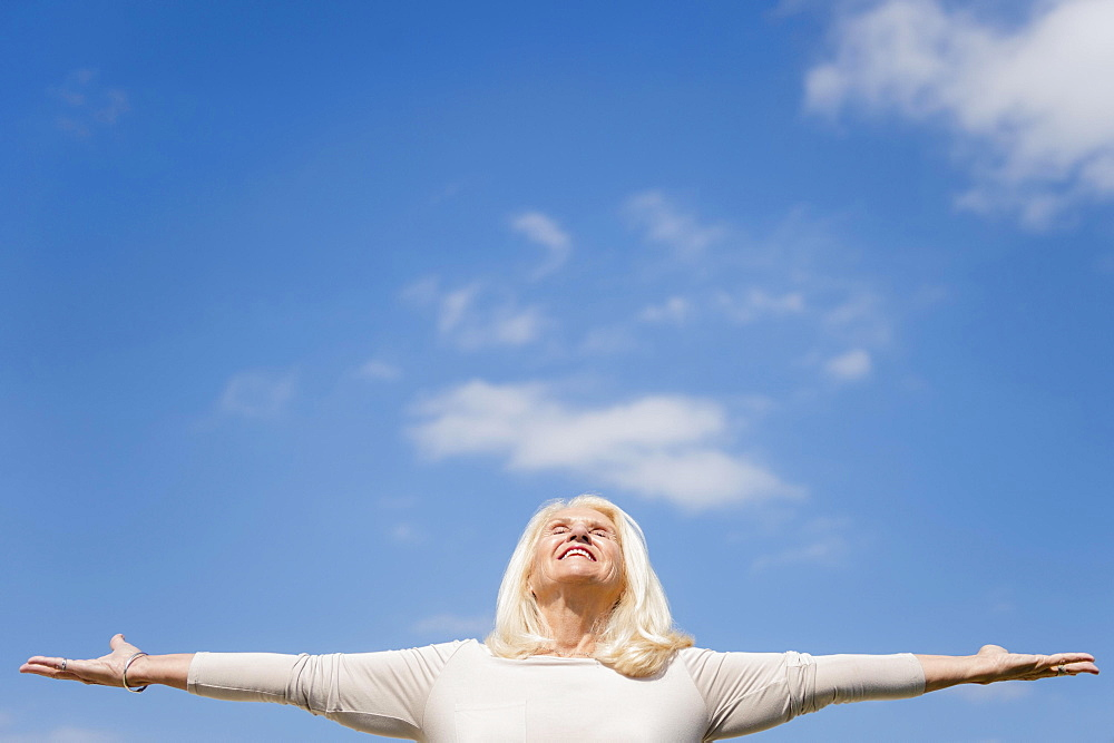 Upward view of senior woman with arms outstretched