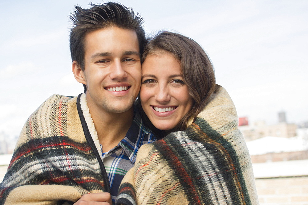 Portrait of young couple wrapped in blanket, Brooklyn, New York