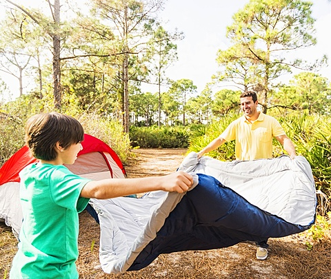 Father and son (12-13) preparing sleeping bag for camping, Jupiter, Florida