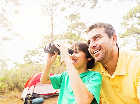 Father and son (12-13) using binoculars, Jupiter, Florida