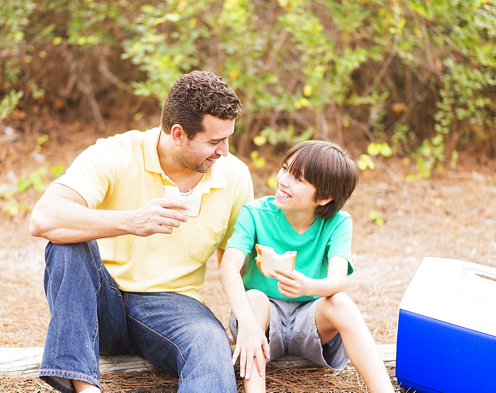 Father and son (12-13) eating sandwiches in forest, Jupiter, Florida