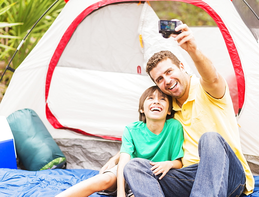 Father and son (12-13) taking selfie in front of tent, Jupiter, Florida
