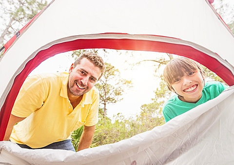 Portrait of father and son (12-13) looking into tent, Jupiter, Florida