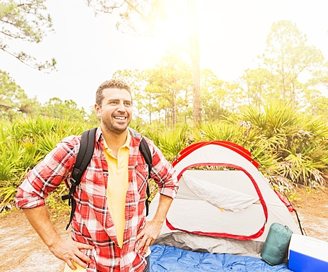 Man with backpack in front of tent, Jupiter, Florida